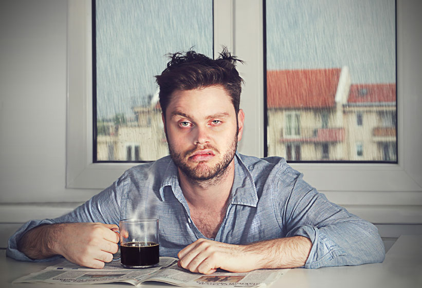 Tired man sitting at a table with a scowl on his face, newspaper open, and drinking coffee