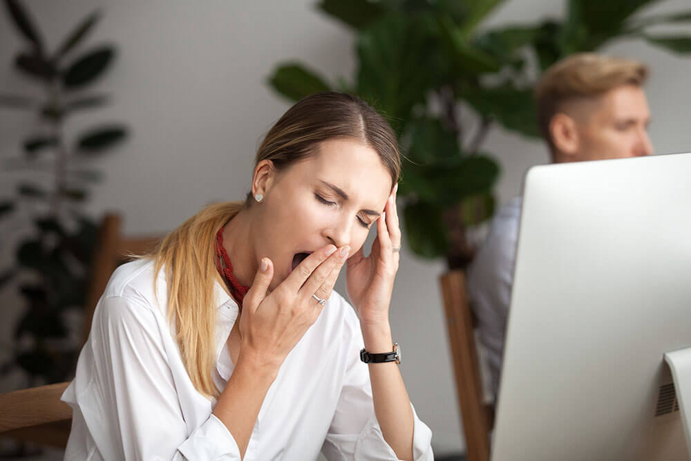 Woman yawning with her hand to her mouth while sitting at a computer