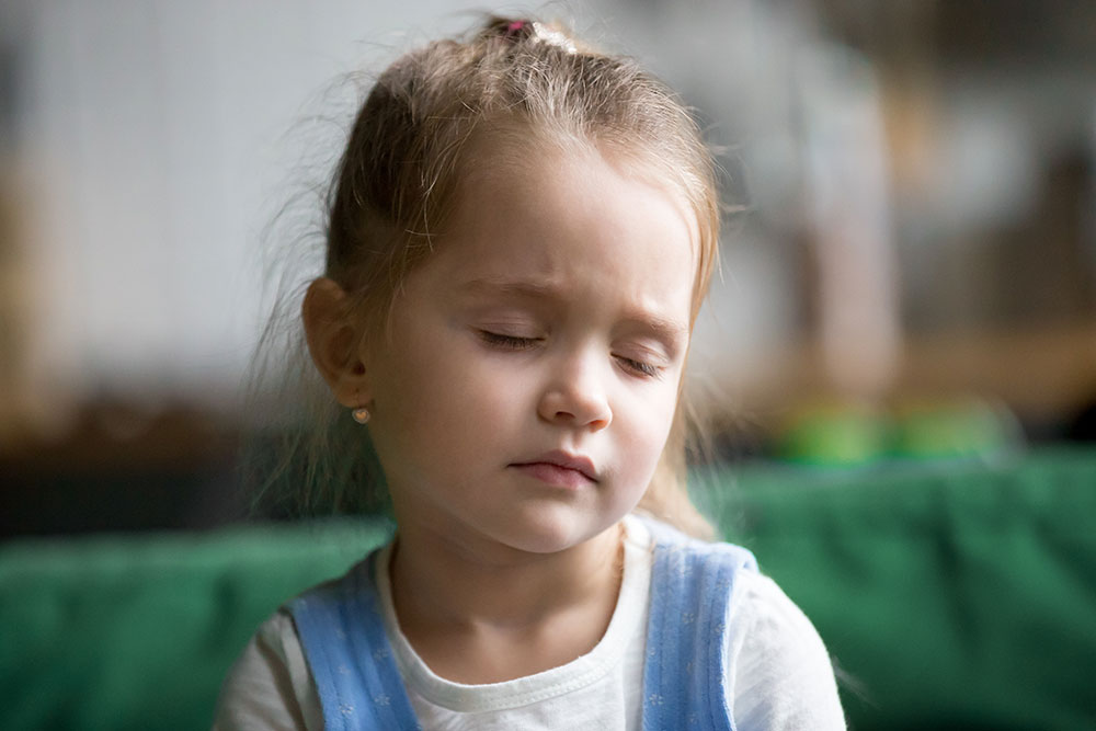 Little girl with her eyes closed, looking tired and sleepy